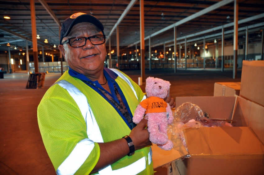 Felix Lugo discovers a box of Texas Strong teddy bears among the pallets of Hurricane Harvey donations.